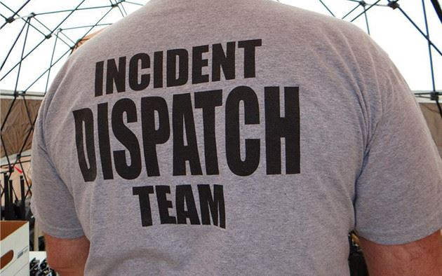 Mean wearing a grey shirt shirt that says &#34incident dispatch team&#34 on the back